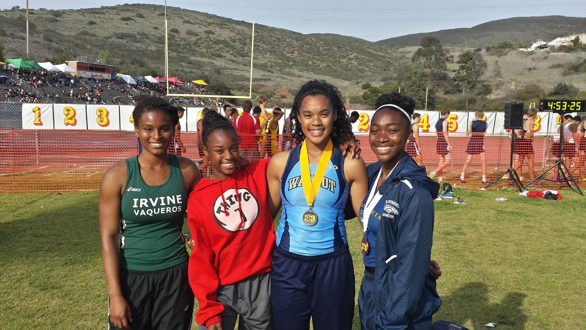Kayla Richardson with medal around neck and team mates.